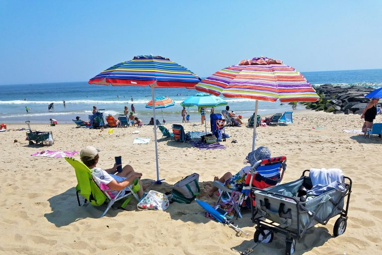 Beverly Jaker of Woodbridge (right) and her sister, Marilyn, lounge under beach umbrellas in Manasquan on July 29, 2019. (Nicholas Pugliese/WHYY)