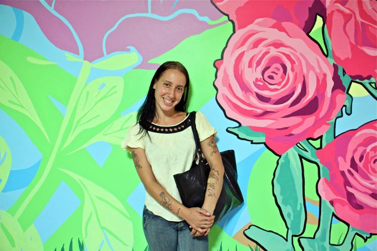 Becky Green, 27, stands in front of the mural she helped to create in SEPTA Suburban Station. (Emma Lee/WHYY)