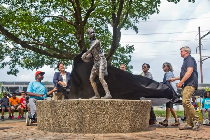 "Sculptor Brian McCutcheon and other city officials unveil McCutcheon's work ""MVP"" at Smith Playground in South Philadelphia. The statue honors Ora Washington, a legendary Philadelphia basketball and tennis player. (Kimberly Paynter/WHYY)"