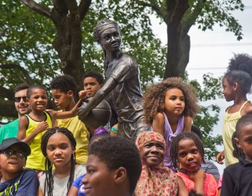 """Smith Playground summer camp participants, and Boys and Girls Club members take the first photos in from of the """"MVP"""" Ora Washington statue. (Kimberly Paynter/WHYY)"""