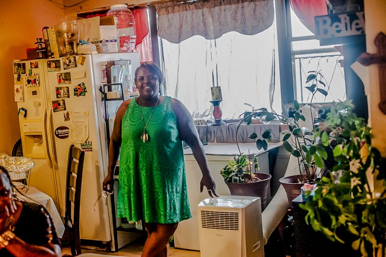 Sheila Armstrong stands in the living room of her 13th floor apartment at the Harrison Plaza buidling at 1050 North 10th Street where she installed an A/C unit to deal with the summer heat. (Brad Larrison for WHYY)