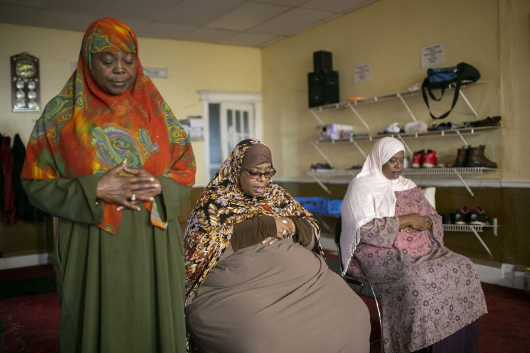 Stephanie Adams (left) prays during a Millati Islami meeting in Camden, N.J. (Miguel Martinez for WHYY)