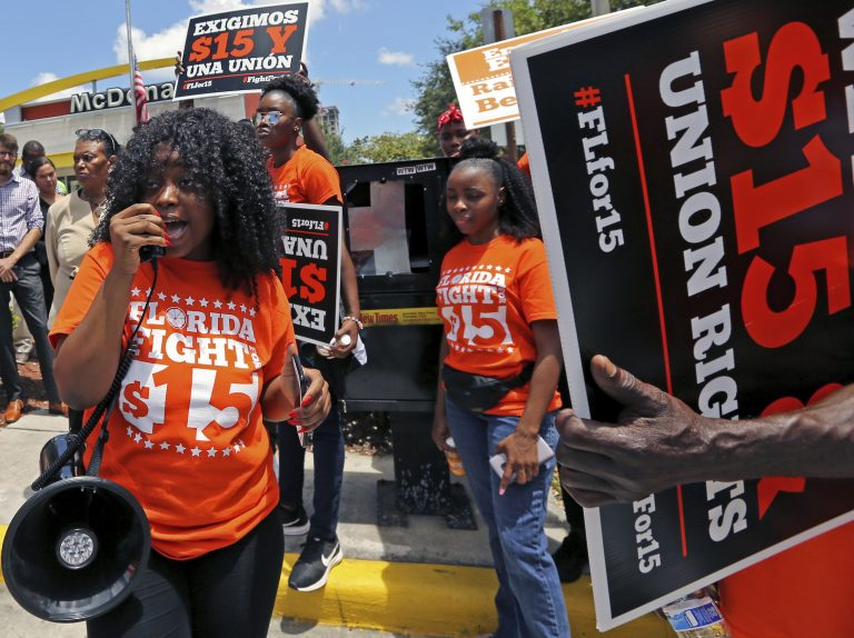 Noji Olaigbe, left, from the Fight for a $15 Minimum Wage movement speaks during a McDonald's workers strike as part of the nationwide movement, at the McDonald's at 27 West Broward Blvd. in Fort Lauderdale, Fla. on Thursday, May 23, 2019. (David Santiago/Miami Herald via AP)