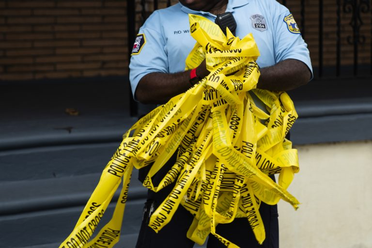 An officer removes crime scene tape after the investigation of what police say was a shooting with one victim in Philadelphia, Wednesday, June 19, 2019. (Matt Rourke/AP Photo)