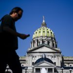 A pedestrian walks by the state Capitol in Harrisburg, Pa., Friday, June 28, 2019. The Pennsylvania House is working to wrap up final budget-season votes two days until the fiscal-year deadline, the morning after grinding to a halt over a critical education bill. (AP Photo/Matt Rourke)