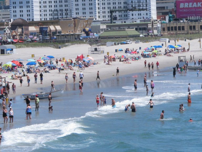 This July 9, 2018 photo shows beachgoers on the shoreline of Atlantic City N.J.  (AP Photo/Wayne Parry)
