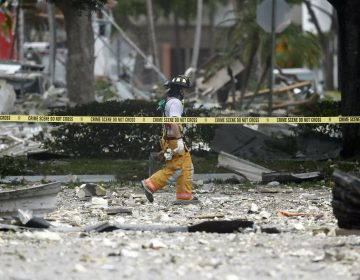 A firefighter walks through the remains of a building after an explosion on Saturday, July 6, 2019, in Plantation, Fla. Several people were injured after a vacant pizza restaurant exploded in the South Florida shopping plaza Saturday, according to police.  The restaurant was destroyed, and nearby businesses were damaged. (Brynn Anderson/AP Photo)