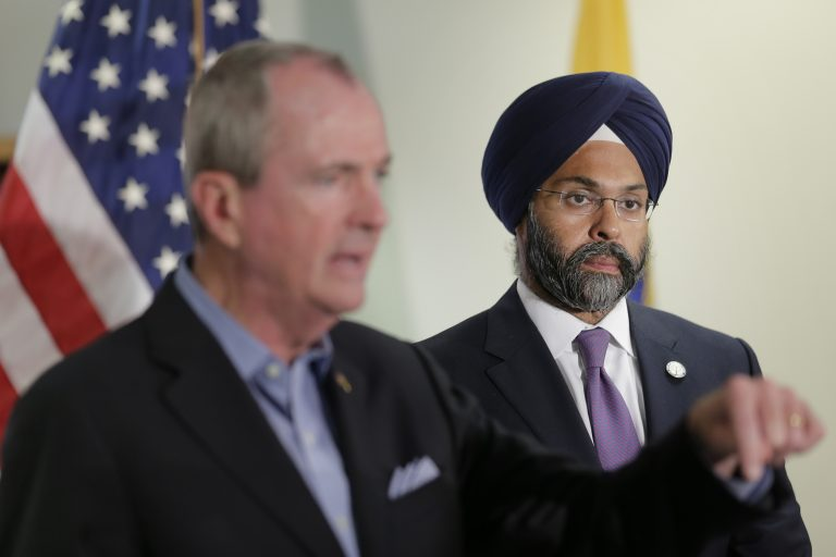 While New Jersey Gov. Phil Murphy, (left), speaks, Attorney General Gurbir Grewal looks on after a bill signing ceremony in Berkeley Heights, N.J., Tuesday, July 16, 2019. Murphy has signed a measure aimed at making so-called smart guns available in the state. He also signed three other measures aimed at reining in gun violence. (Seth Wenig/AP Photo)