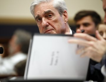 Former special counsel Robert Mueller, checks pages in the report as he testifies before the House Judiciary Committee hearing on his report on Russian election interference, on Capitol Hill, Wednesday, July 24, 2019 in Washington. (Alex Brandon/AP Photo)
