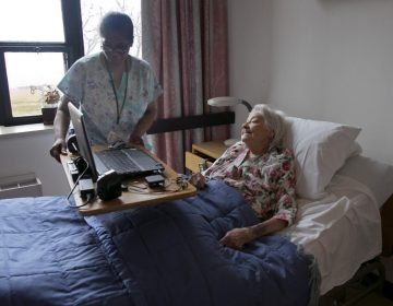 A nurse's aide helps nursing home patient Louise Irving on Wednesday, March 25, 2015. (Richard Drew/AP Photo)