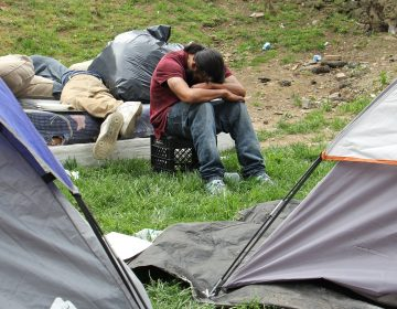 A man rests his head on his arms in a heroin encampment in a vacant lot on Kensington Avenue on May 4, 2018. The encampment was later cleared out by the city. Pennsylvania will receive $10 million from Bloomberg Philanthropies to combat opioid addiction. The state was picked for its diverse cultural geography which could offer models for both rural and urban regions hit hard by high numbers of overdose deaths. (Emma Lee/WHYY)