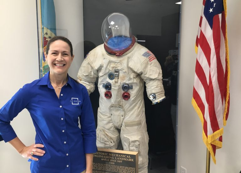 Patty Stoll, senior director and division manager for ILC Dover's space systems division, stands with a suit made at ILC Dover in Frederica, Delaware for the Apollo mission. (Mark Eichmann/WHYY)