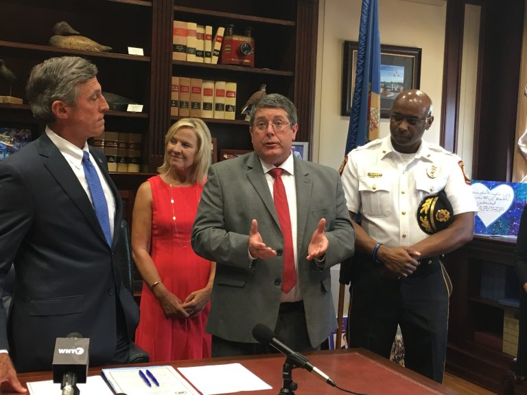Smyrna School District Superintendent Patrick Williams (third from left)talks about legislation allowing police to inform school leaders when a student experiences a traumatic event. (From left) Gov. John Carney, Lt. Gov. Bethany Hall-Long, and Smryna Police Chief Torrie James stand alongside Williams in Carney's Dover office. (Mark Eichmann/WHYY)