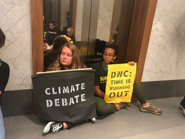 Two protesters take their posts at the elevators. (Naomi Brauner/WHYY)