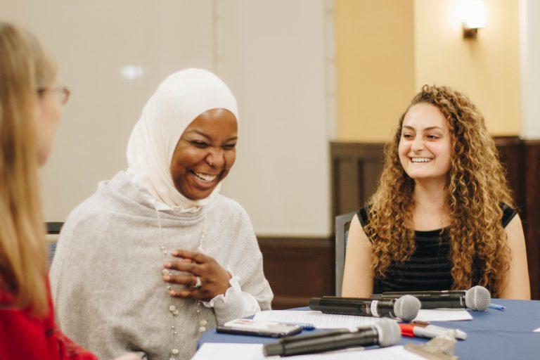 Conversationalists Kameelah Mu'Min Rashad and Emily Zislis share a laugh with WHYY's Jennifer Lynn during A Conversation on Identity and Belonging hosted at the University of Pennsylvania. (Riley Jackson/Interfaith Philadelphia)