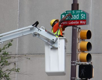 A worker bolts on a sign changing a block of Broad Street Patti LaBelle Way. (Emma Lee/WHYY)