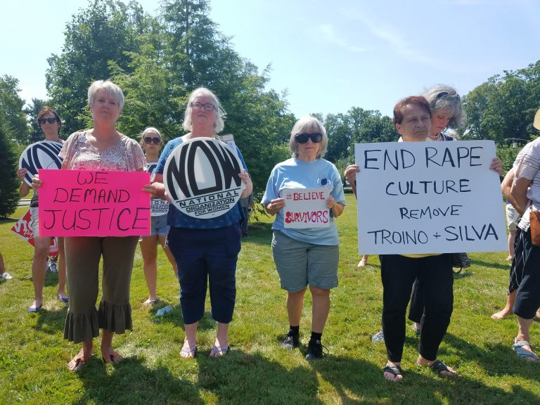 From left, Carol Gay, Joni Brennan Catherine Hunt and JJ Mistretta hold signs at a protest in Freehold to demand the removal of Judges Troiano and Silva on July 11, 2019. (Nicholas Pugliese/WHYY)