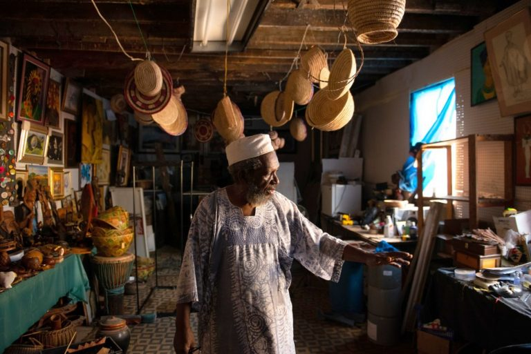 Sharif Abdur-Rahim, one of two founding brothers of West Philadelphia's African Cultural Arts Forum, stands in a second-floor workshop used to store African art and to produce the oils, incense and personal-care products they sell. (Kriston Jae Bethel for NextCity)