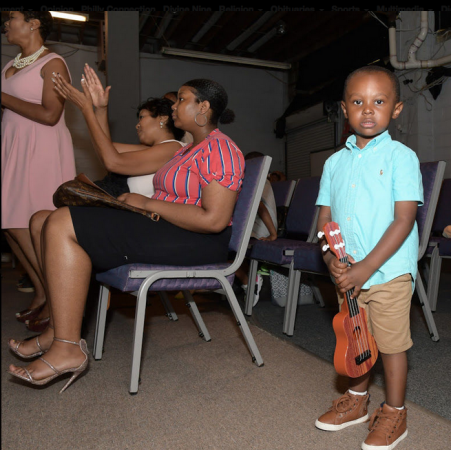 Three-year-old Carter of Truth Church Worship Center holds his guitar during service (Marissa Weekes Mason/The Philadelphia Tribune)