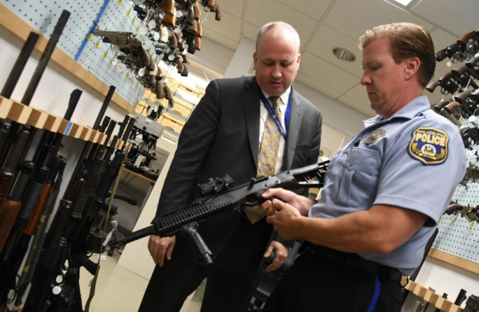 Philadelphia Police Officer Bob Mahan holds a firearm stored in the department's Forensic Science Center beside Michael Garvey, director of the Philadelphia Police Department's Office of Forensic Science (Abdul Sulayman/The Philadelphia Tribune)
