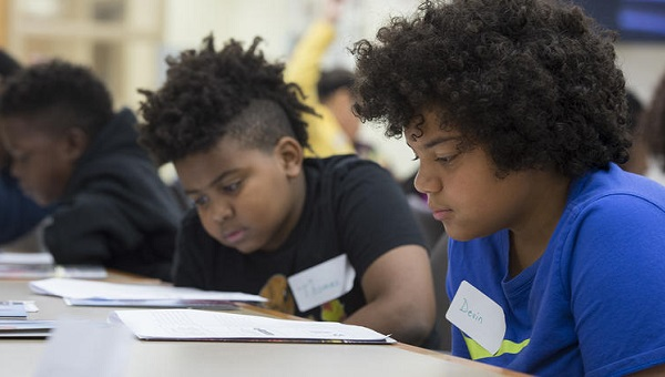 Fifth-graders Thomas Medley, (left), and Devin Walker study their training materials as they learn to become student leaders at Woodland Hills Intermediate in 2017. (The University of Pittsburgh)