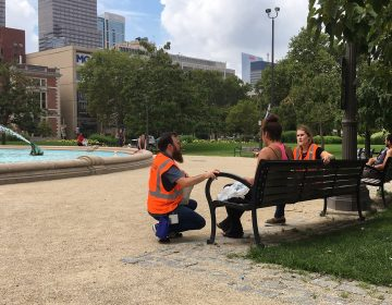 Pre-heat wave, Kevin Riordan (left) and Carrie Wagner offer services to a person experiencing homelessness. MICHAELA WINBERG / BILLY PENN