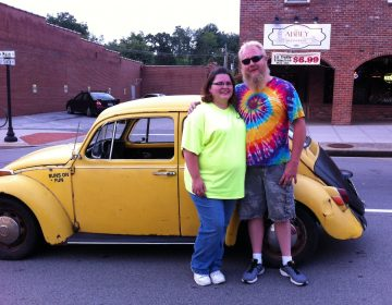 Jessica Bray and her husband, Anthony Bray, pose with their 1970 Volkswagen Beetle. Anthony converted his Beetle to an electric car.