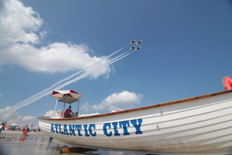 The U.S. Air Force Thunderbirds Air Demonstration Squadron starts their show over the beaches of Atlantic City, N.J. as lifeguard Ryan McCline watches bathers on Aug. 13, 2014. (U.S. Air National Guard photo by Tech. Sgt. Matt Hecht)