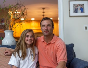Lexi DiMarino and her father, Keith DiMarino, sit for a portrait in their Wayne, Pennsylvania home. Following a migraine that Lexi endured for 100 days in a row, the father-daughter pair have become outspoken advocates for pediatric migraine awareness. (Angela Gervasi for WHYY)