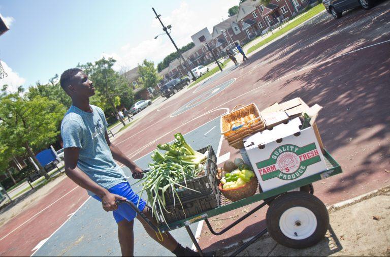 Ahmaj Jackson, 14, wheels fresh produce around the Ruth Bennett Community Farm in Chester, Pennsylvania. (Kimberly Paynter/WHYY)