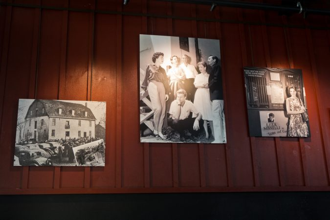 Historic images of the Bucks County Playhouse (left), Robert Redford on stage (center) and Liza Minelli (right) hang in The Deck, a restaurant attached to the Bucks County Playhouse in New Hope, Pa. (Kimberly Paynter/WHYY)