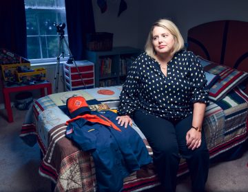 Leslie Slingsby, executive director of Mission Kids, sits on her sons bed with his Boy Scouts of America uniform and handbook at her Collegeville, Pa. home on August 14, 2019. Slingsby's nonprofit works on behalf of Montgomery County to investigate claims of child abuse and advocates for child protection around the world. (Kriston Jae Bethel for WHYY)