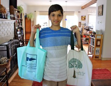 Kiran Schatz, 12, carries his school supplies home in reusable bags. The West Chester student and his classmates worked to promote legislation that would ban the use of disposable plastic bags in their town. (Emma Lee/WHYY)