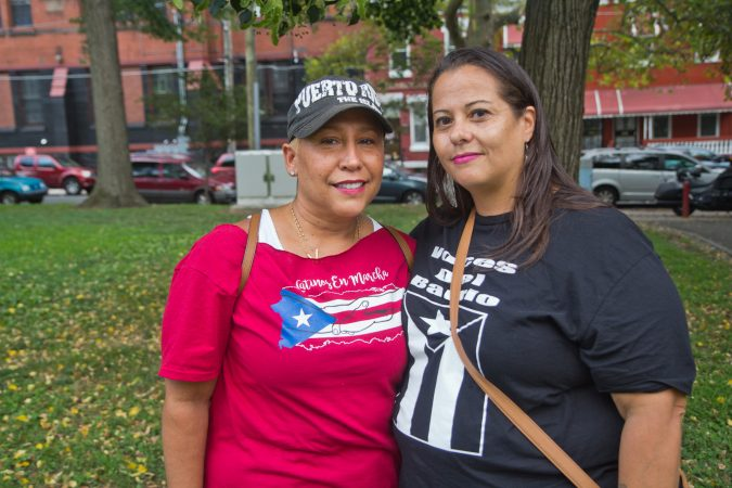 Organizers Kimberly Lamberti of Latinos En Marcha and Ana Montañez, with Voces del Barrio, celebrate the resignation of Puerto Rican governor Ricardo Rosselló at Fairhill Square in Kensington. (Kimberly Paynter/WHYY)