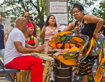 Bomba drummer Jose Emmannuelli Nater plays for Rochel Rojas as she dances at the celebration of the resignation of Puerto Rican governor Ricardo Rosselló at Fairhill Square in Kensington. (Kimberly Paynter/WHYY)