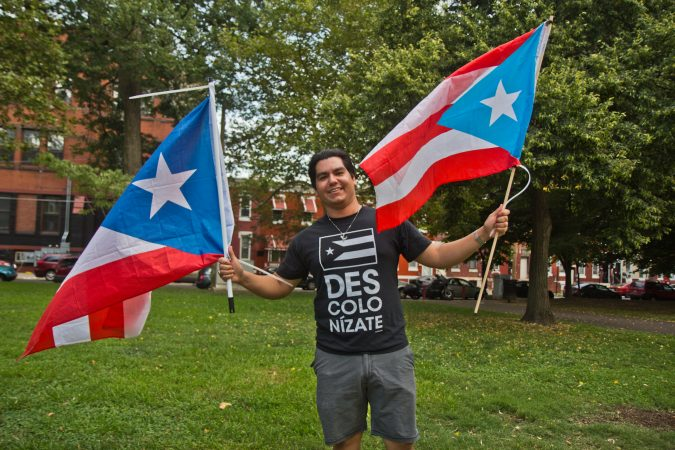 Adrian Mercado flies two Puerto Rican flags at the celebration of the resignation of Puerto Rican governor Ricardo Rosselló at Fairhill Square in Kensington. (Kimberly Paynter/WHYY)