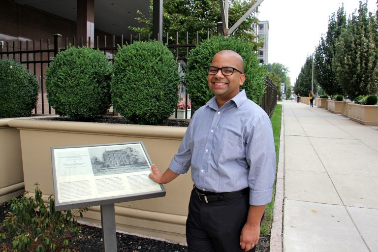 Samip Mallik, director and co-founder of the South Asian American Digital Archive, stands at 6th and Arch streets, the former site of the Female Medical College of Pennsylvania. (Emma Lee/WHYY)