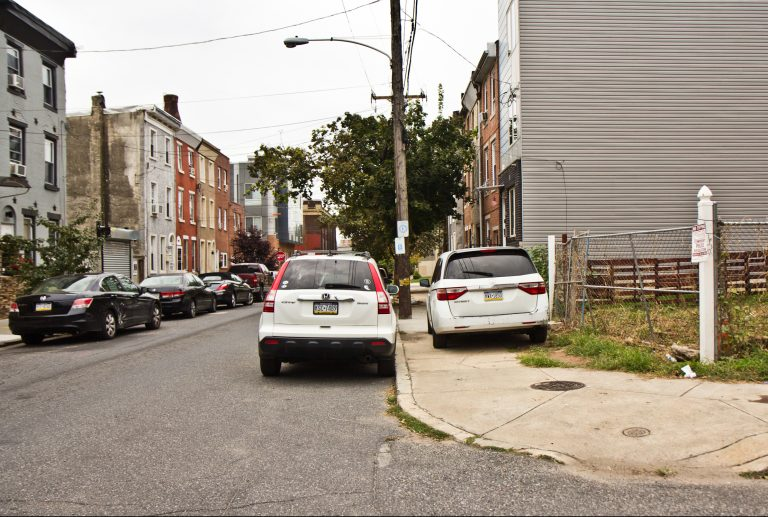 Cars park on the sidewalk on Coral Street in Philadelphia's rapidly developing East Kensington neighborhood. (Kimberly Paynter/WHYY)