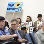 Signs are held up as a standing room only crowd listens to testimony given by environmental experts, community activists and residents during a community meeting regarding the future of the site of Philadelphia Energy Solutions in August 2019. (Bastiaan Slabbers for WHYY)