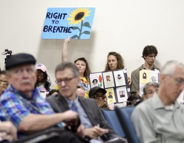 Signs are held up as a standing room only crowd listens to testimony given by environmental experts, community activists and residents during a community meeting by the city's Refinery Advisory Group regarding the future of the site of Philadelphia Energy Solutions. (Bastiaan Slabbers for WHYY)