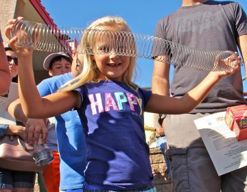 Maura McGlensey, 6, of Clifton Heights, plays with a Slinky during the dedication ceremony of a historical marker commemorating the manufacture of the popular toy at James Industries in Clifton Heights. (Emma Lee/WHYY)