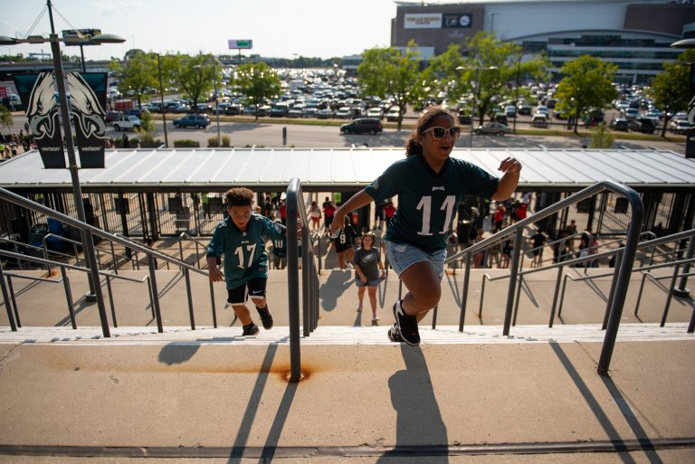 Isaac and Jazzy Dyer, from Harrisburg, Pa., run up the steps to Lincoln Financial Field before the start of open practice on Sunday, August 4, 2019. (Kriston Jae Bethel for WHYY)