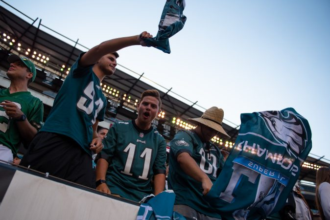 Ethan Minshall, Noah Carter and Nik Boone cheer along to the Eagle's fight song during open practice at Lincoln Financial Field on Sunday, August 4, 2019. (Kriston Jae Bethel for WHYY)