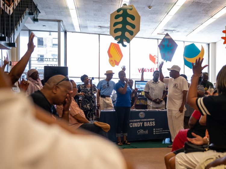 Hands are raised in response to Councilwoman Cindy Bass asking people who has experienced gun violence during a community meeting at the Nicetown-Tioga Library on Saturday, August 17, 2019. (Kriston Jae Bethel for WHYY)