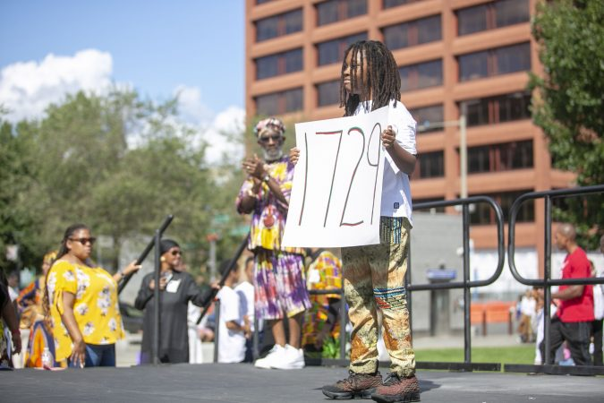 Qahhaaru Re-Imhotep, 10, wals on stage representing the year 1729 during an event to commemorate the 400th anniversary of the first arrival of enslaved Africans at the President's House. (Miguel Martinez for WHYY)