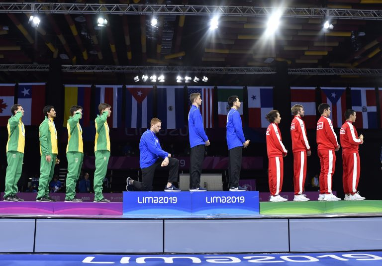 In this Friday, Aug. 9, 2019 photo, released by Lima 2019 News Services, Race Imboden of the United States takes a knee, as teammates Mick Itkin and Gerek Meinhardt stand on the podium after winning the gold medal in team's foil, at the Pan American Games in Lima, Peru. 'Racism, gun control, mistreatment of immigrants, and a president who spreads hate are at the top of a long list' of America's problems, Imboden said in a tweet sent after his medals ceremony. 'I chose to sacrifice my moment today at the top of the podium to call attention to issues that I believe need to be addressed.' (Jose Sotomayor/Lima 2019 News Services via AP)