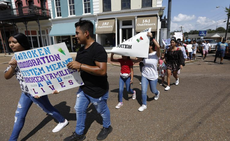 In this Aug. 11, 2019 photo, children of mainly Latino immigrant parents hold signs in support of them and those individuals picked up during an immigration raid at a food processing plant in Canton, Miss., following a Spanish Mass at Sacred Heart Catholic Church in Canton, Miss. Trump administration rules that could deny green cards to immigrants if they use Medicaid, food stamps, housing vouchers or other forms of public assistance are going into effect. (Rogelio V. Solis./AP Photo)