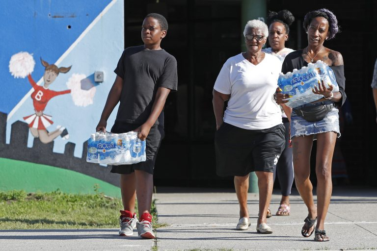 Rahjiah McBride, of Chester, Pa., (right), helps her relatives, Newark residents Elnora and Bowdell Goodwin, center and second right, as Goodwin's son pitches in carrying bottled water from the Boylan Street Recreation Center, Monday, Aug. 12, 2019, in Newark, N.J. (Kathy Willens/AP Photo)