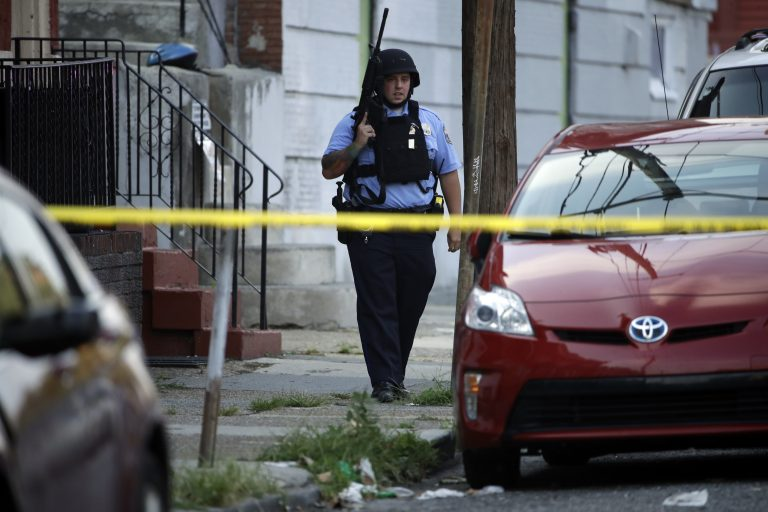 A police officer patrols the block near a house as they investigate an active shooting situation, Wednesday, Aug. 14, 2019, in the Nicetown neighborhood of Philadelphia. (AP Photo/Matt Rourke)