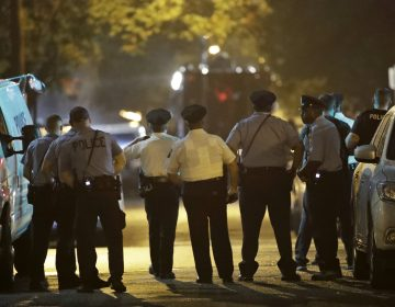 Policer officers watch as a gunman is apprehended following a standoff Wednesday, Aug. 14, 2019, in Philadelphia. (AP Photo/Matt Rourke)